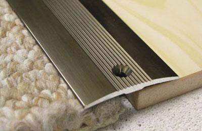 У порога ковролин закрепляется металлической рейкой