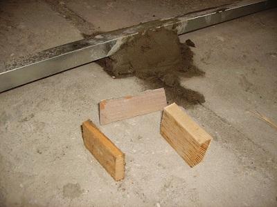 Использование кусочков древесины для выравнивания маяков